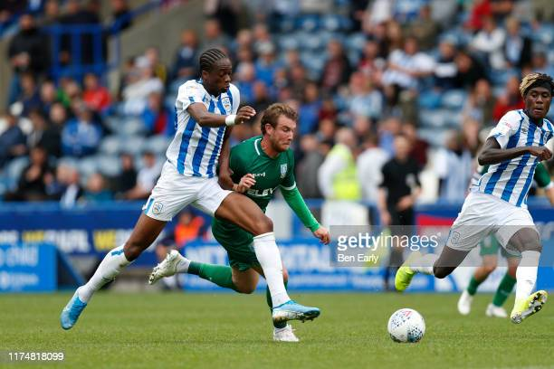 Sam Winnall of Sheffield Wednesday and Terence Kongolo of Huddersfield Town chase after the ball during the Sky Bet Championship match between...