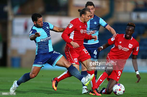 Sam Wood and Stephen McGinn of Wycombe Wanderers battle Luke Freeman and Tammy Abraham of Bristol City during the EFL Cup match between Wycombe...