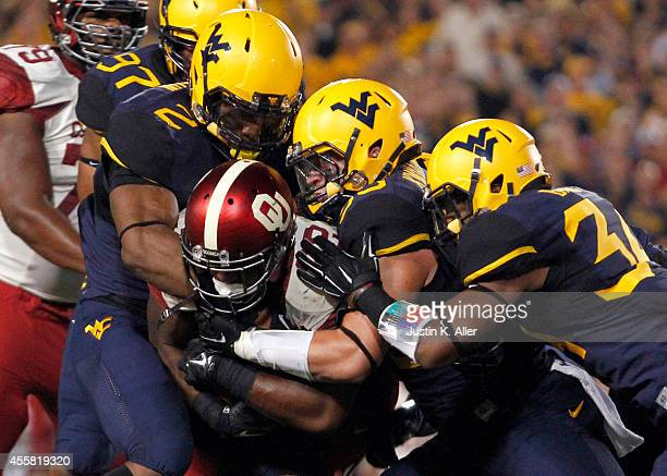 Samaje Perine of the Oklahoma Sooners is stopped by Brandon Golson and Ishmael Banks of the West Virginia Mountaineers in the first half during the...