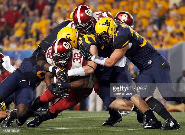 Samaje Perine of the Oklahoma Sooners rushes against Wes Tonkery and Carlton Nash of the West Virginia Mountaineers in the first half during the game...