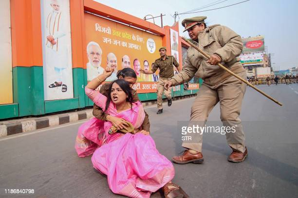 Samajwadi Party activist is being held by police personnel as she protests against the recent Unnao rape case during a demonstration at Vishan Sabha...