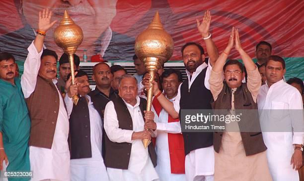 Samajwadi Party Chief Mulayam Singh Yadav and his brother Shivpal Singh Yadav lifting mace presented by party workers during a campaign rally at...