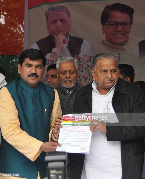 Samajwadi Party chief Mulayam Singh Yadav poses with Pasmanda Samaj president Anis Mansoori at an event announcing the merger of Pasmanda Samaj with...