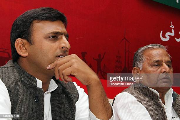 Samajwadi Party chief Mulayam Singh Yadav sits with his son Akhilesh Yadav at press conference at the party office on March 9, 2012 in Lucknow,...