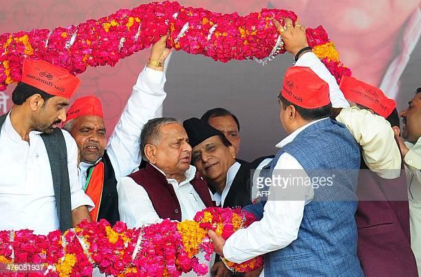 Samajwadi Party Supremo Mulayam Singh Yadav with party leader Mohammad Azam Khan is greeted with a garland by Samajwadi leaders during a public rally...