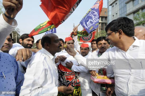 Samajwadi Party workers along with BSP members celebrate after winning the Lok Sabha election seats in Uttar Pradesh on March 14 2018 in Noida India...