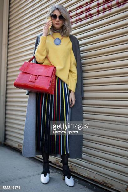 Samantha Angelo is seen attending ICB during New York Fashion Week wearing a grey wool coat yellow sweater striped skirt and red bag on February 14...