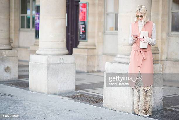 Samantha Angelo poses wearing a Malene Birger coat Acne Studios jumper and Dior pants before the Isabel Marant show at Place Colette during Paris...