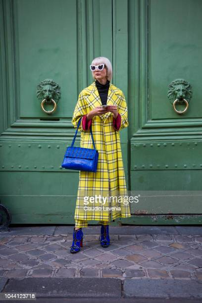 Samantha Angelo wearing yellow checked trench coat and blue bag is seen after the Jacquemus show on September 24 2018 in Paris France