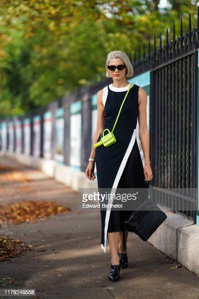 Samantha Angelo wears sunglasses, a black and white sleeveless dress, a neon green shoulder strapped mini bag, outside Lacoste, during Paris Fashion...