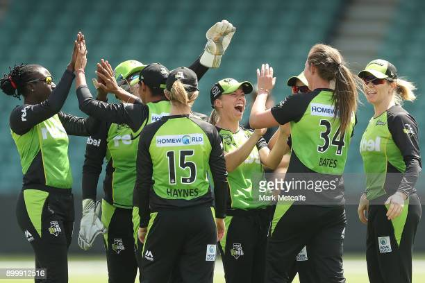 Samantha Bates of the Thunder celebrates with team mates after taking the wicket of Hayley Matthews of the Hurricanes during the Women's Big Bash...