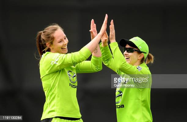 Samantha Bates of the Thunder is congratulated by team mates after getting a wicket during the Women's Big Bash League match between the Melbourne...