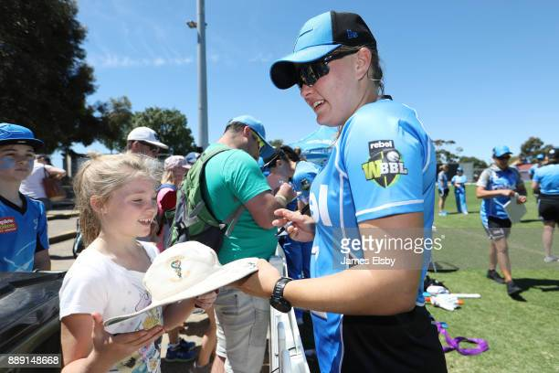 Samantha Betts of the Adelaide Strikers signs for a young fan during the Women's Big Bash League WBBL match between the Strikers and the Hurricanes...