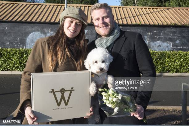 Samantha Brooke and Alex Jablonskas pose with their dog 'Poppy' as they wait to greet Prince Harry and fiancee Meghan Markle during a visit to staff...