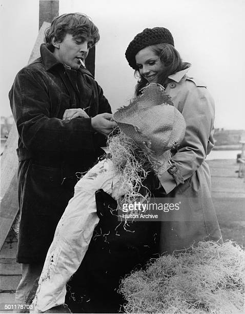 Samantha Eggar holds up a scarecrow as David Hemmings looks at it in a scene of the movie The Walking Stick circa 1970