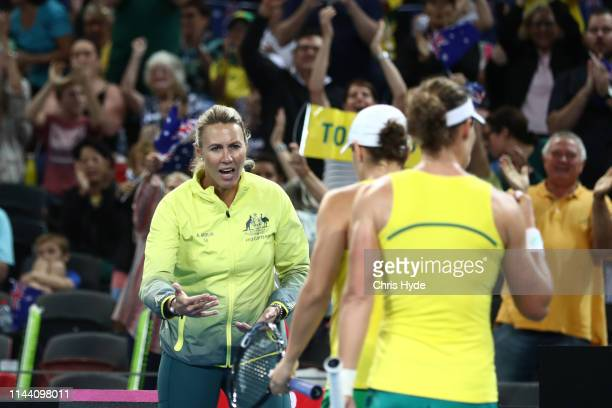 Samantha Stosur and Ashleigh Barty of Australia celebrate a point with Captain Alicia Molik in their doubles match against Victoria Azarenka and in...