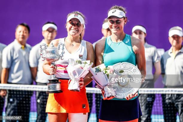 Samantha Stosur of Australia poses for photos with second-placed Sofia Kenin of the US after their women's singles final match at the Guangzhou Open...