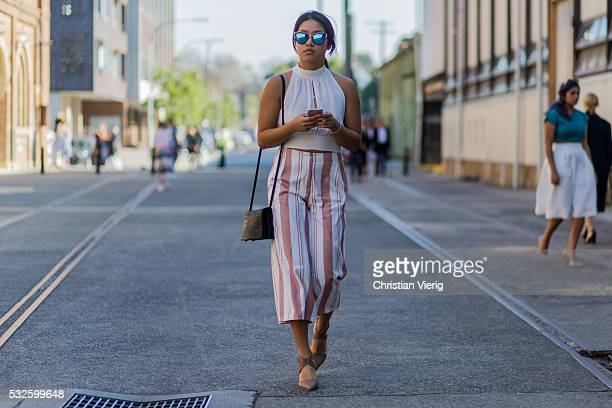 Samantha Toong wearing a white Quay tank top and white nude striped pants and Windsor heels at MercedesBenz Fashion Week Resort 17 Collections at...