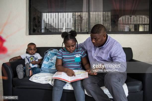 Samara is homeschooled by her dad Samy Janvier while her little brother Samy Jr watches in Delmas south of PortauPrince on November 20 2019 The...