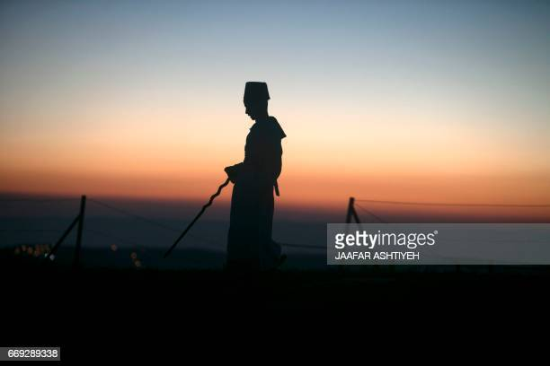 A Samaritan worshiper takes part in a Passover ceremony at Mount Gerizim near the northern West Bank city of Nablus early on April 17 2017 The...