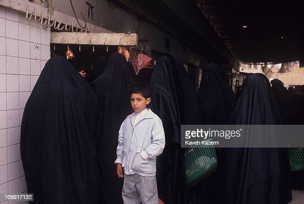Young Iraqi boy stands amidst women in black chadors queuing outside a butcher shop during the Gulf War, 23rd February 1991.