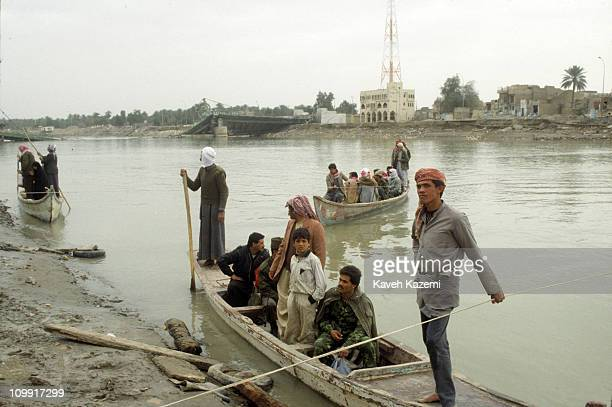 Iraqis cross the Euphrates river on boats after one of the city bridges was hit and downed by Allied forces bombers during Operation Desert Storm...