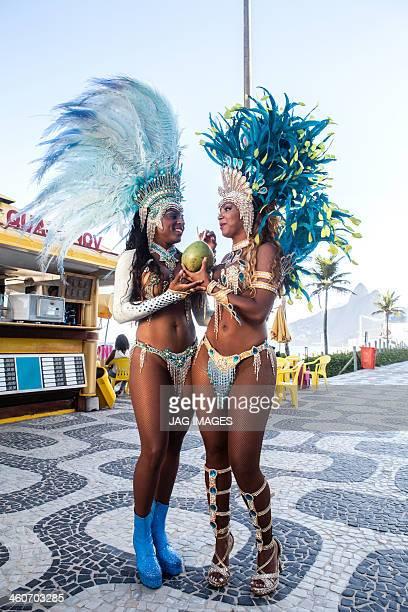 Samba dancers drinking coconut drink, Ipanema Beach, Rio De Janeiro, Brazil