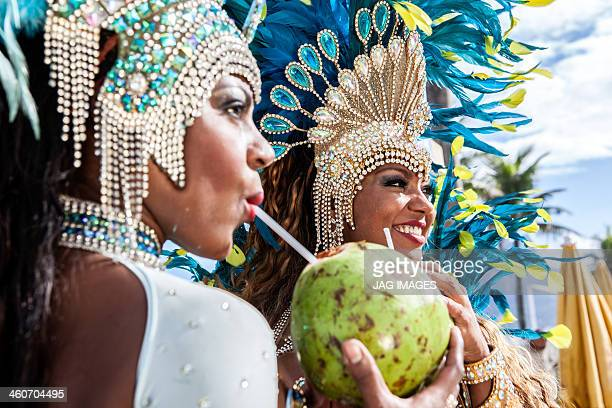 samba dancers in costume, drinking coconut drinks, ipanema beach, rio de janeiro, brazil - carnaval rio photos et images de collection