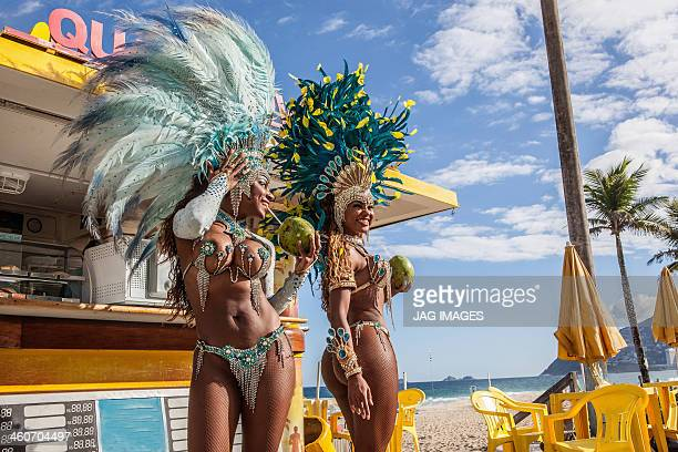 samba dancers in costume with coconut drinks, ipanema beach, rio de janeiro, brazil - brasil stock pictures, royalty-free photos & images