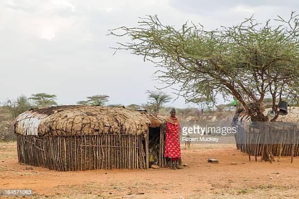 Samburu Lady wearing red waiting outside her home in Samburu for the return of her husband, goats and cattle. Samburu house is made of sticks and...