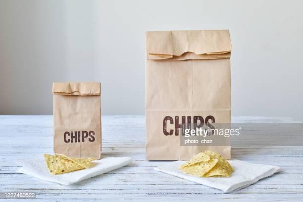 zelfde portie chips voor de grote & kleine tas - portie stockfoto's en -beelden