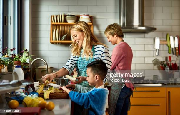 same sex couple cooking with son in kitchen - lgbtq  and female domestic life fotografías e imágenes de stock