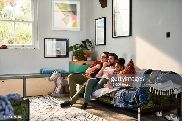 same sex couple eating popcorn with daughter on sofa - couple relationship stock pictures, royalty-free photos & images
