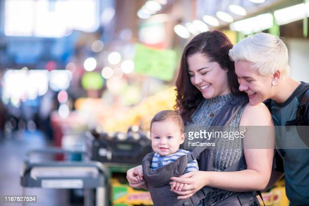 same sex couple grocery shop with their son at a local market - mom son sex photo stock pictures, royalty-free photos & images