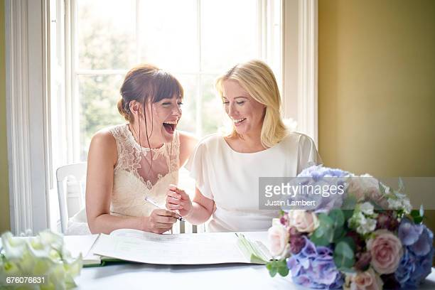 Same sex couple laughing signing marriage register