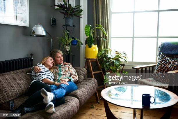 same sex couple lying on sofa cuddling - lgbtq  and female domestic life fotografías e imágenes de stock