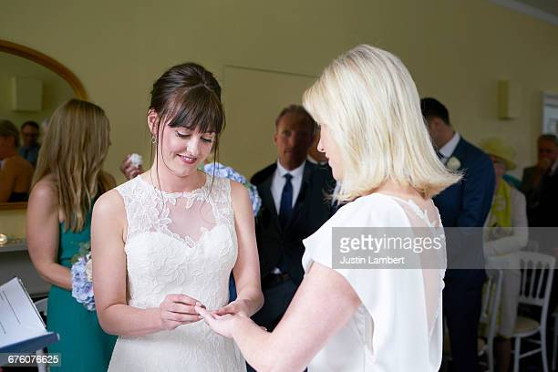 Same sex couple marrying placing ring on finger
