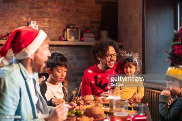 same sex family out for christmas dinner - adoption stock pictures, royalty-free photos & images