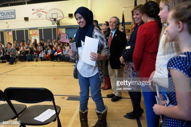 Sameen Abbasi formerly of Pakistan faces the crowd with her certificate of citizenship from Immigration Judge Ivan Gardzelewski after taking the Oath...