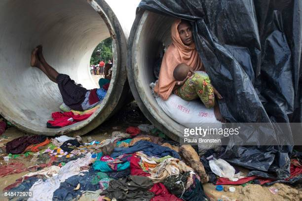 Sameera looks our from a cement cylinder holding her 7 month old baby where the family are living until a shelter is built September 17 2017 in...