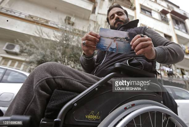 Samer al-Sawwan, a 33-year-old wheelchair-bound Syrian poses for a picture in the capital Damascus on March 1 while holding a photo of himself from...