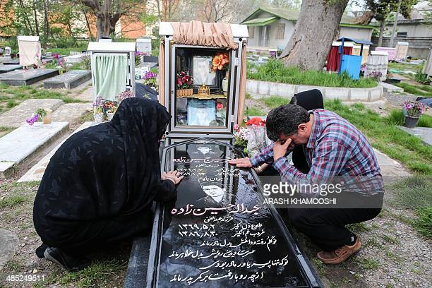 Samereh Alinejad and Abdolghani Hosseinzadeh mourn at the grave of their son Abdolah Hosseinzadeh who was killed by a fellow Iranian Balal in a...