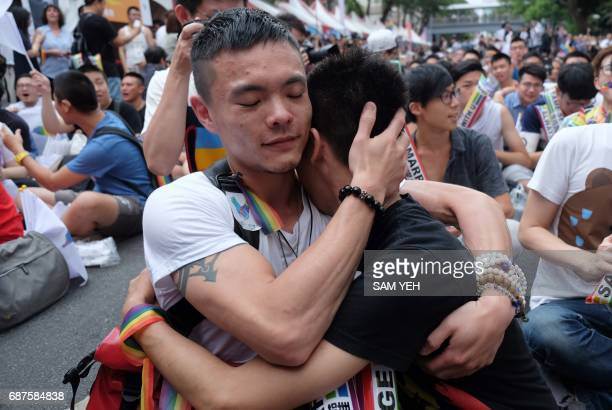 Samesex activists hug outside the parliament in Taipei on May 24 2017 as they celebrate the landmark decision paving the way for the island to become...