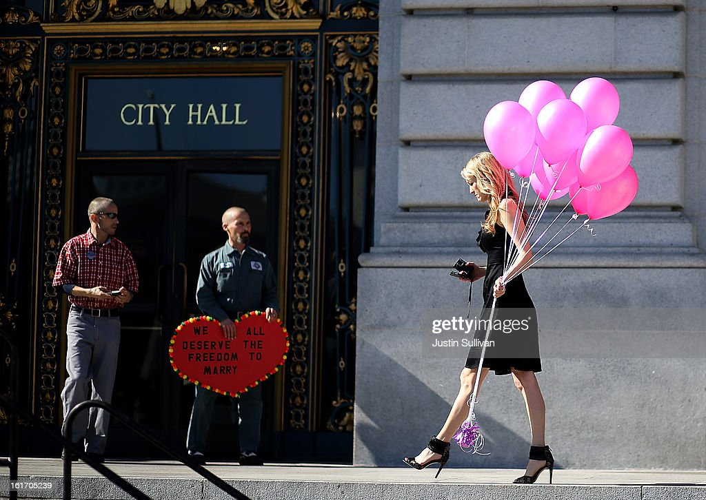 Same-sex couple Frank Capley (C) and Joe Alfano (L) look on as a woman carries Valentine's balloons in front of San Francisco City Hall on February 14, 2013 in San Francisco, California. Close to a dozen same-sex couples who were denied marriage licenses were arrested after they staged a sit-in demonstration inside the office of San Francisco's county clerk.