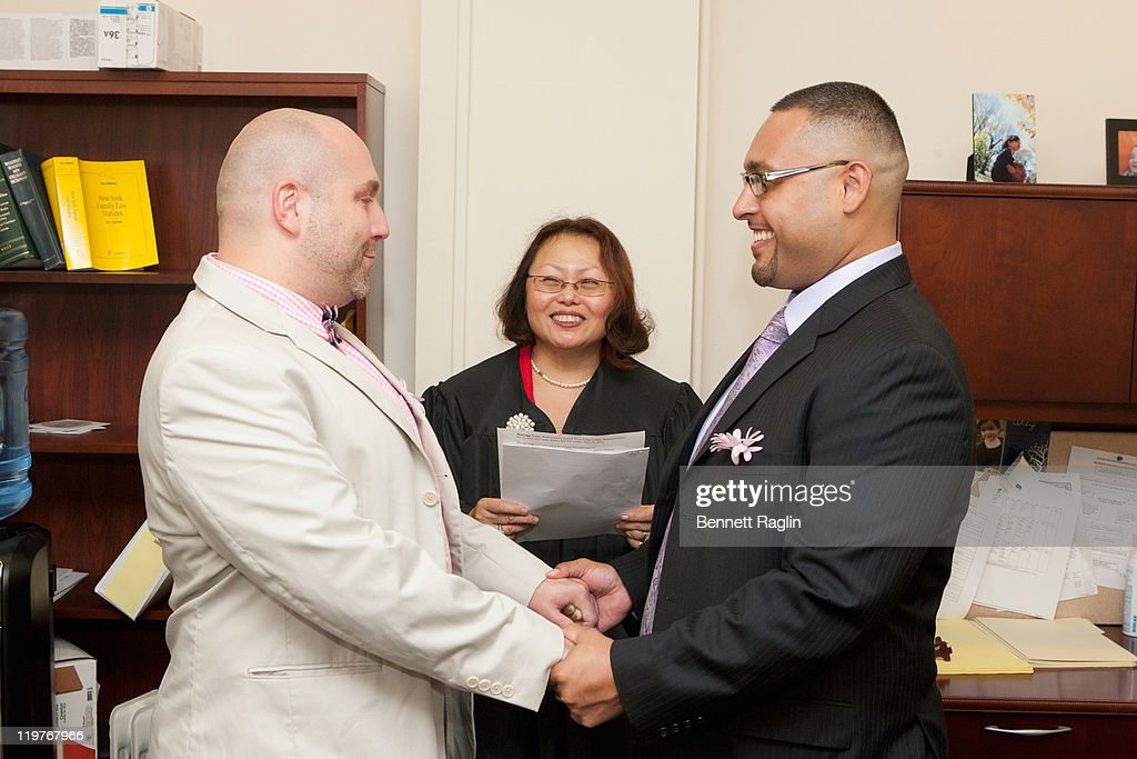 Same-sex couple John Chaich and Matthew Bautista takes their wedding vows while New Yorlk Supreme Court Justice Doris Ling-Cohan (C) officiates during the first day of legal same-sex marriage in New York State on July 24, 2011 in New York City.