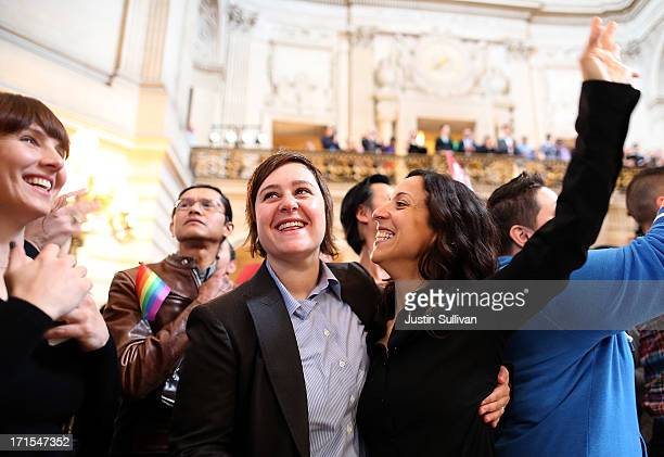 Samesex couple Lori Bilella and Renara Moreira react to results from the US Supreme Court's rulings on gay marriage in City Hall June 26 2013 in San...