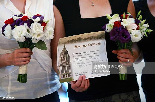 Samesex couple Shani Lyons and Melanie Franklin hold their marriage certificate as the pose for family photos after their wedding ceremony October 15...