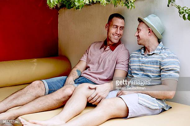 A same-sex couple sitting outside together.