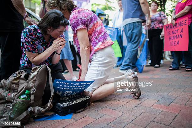 Samesex marriage protestors pray in front of the 4th US Circuit Court of Appeals before a court hearing May 13 2014 in Richmond Virginia Three judges...