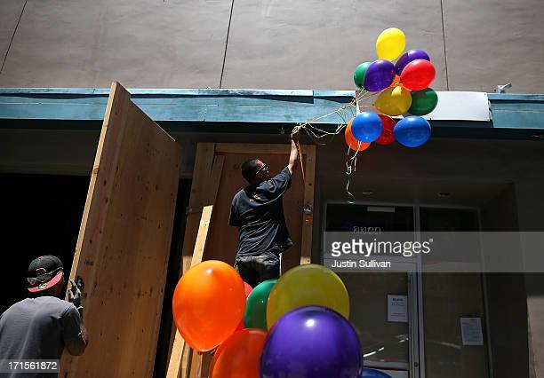 A samesex marriage supporter hangs balloons in the colors of the pride flag on June 26 2013 in San Francisco California The Supreme Court of the...